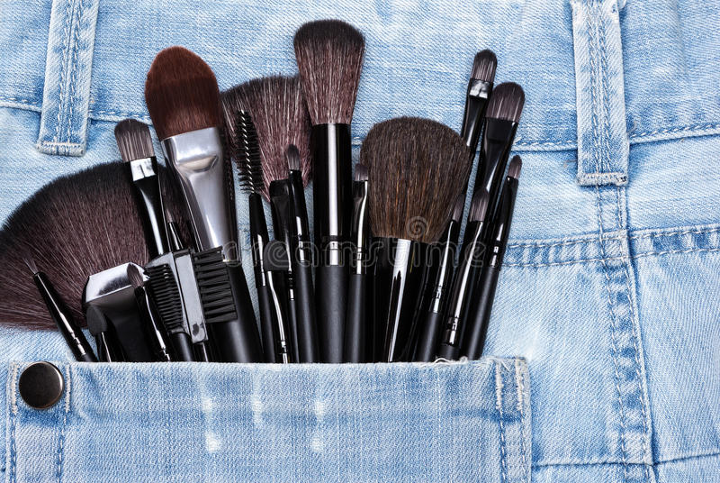 Applicators and makeup brushes in jeans pocket. Professional tools of make-up artist in shabby jeans pocket. Sponge tip applicators and various makeup brushes stock image