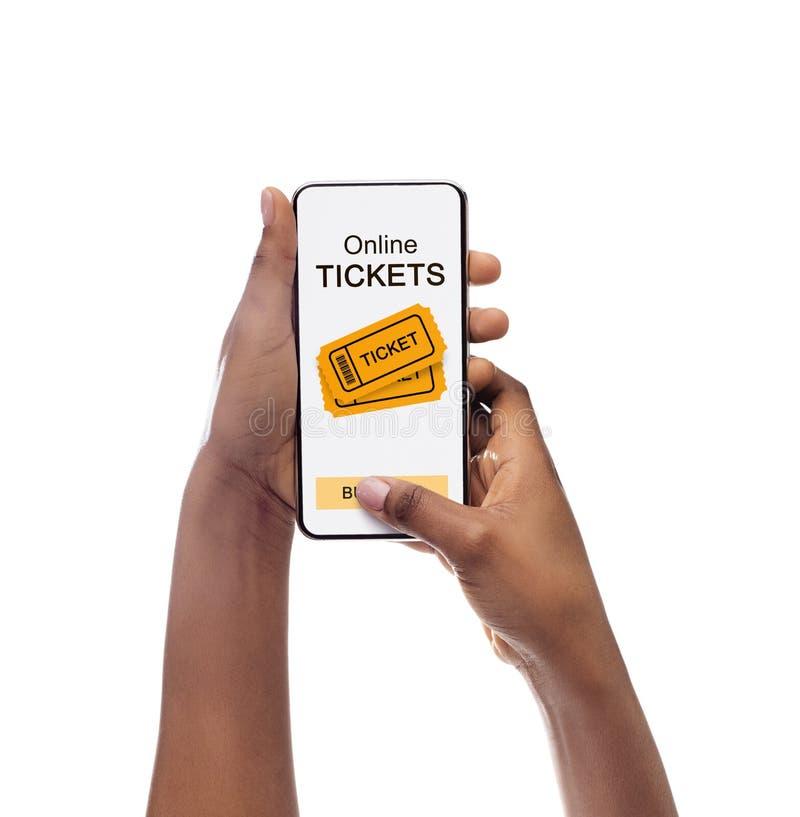 Applicazione dei biglietti di evento sullo schermo del cellulare in mani della ragazza nera fotografie stock libere da diritti