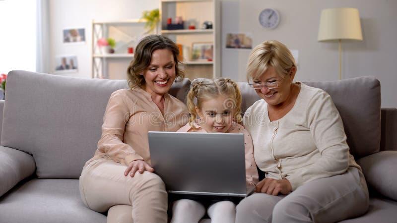 Applicazione del computer portatile di uso del bambino di insegnamento della figlia e della nonna, giocante gioco fotografia stock libera da diritti
