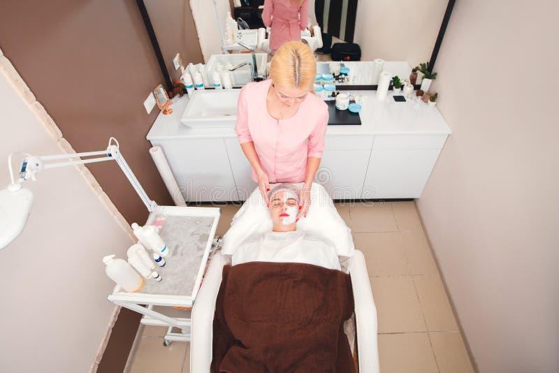 Applicazione della crema facciale sulla pelle del fronte della giovane donna immagine stock libera da diritti