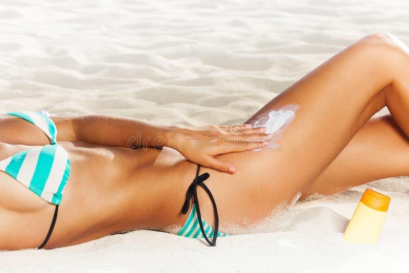 Applicazione della protezione solare sul corpo bene a forma di della spiaggia immagine stock libera da diritti