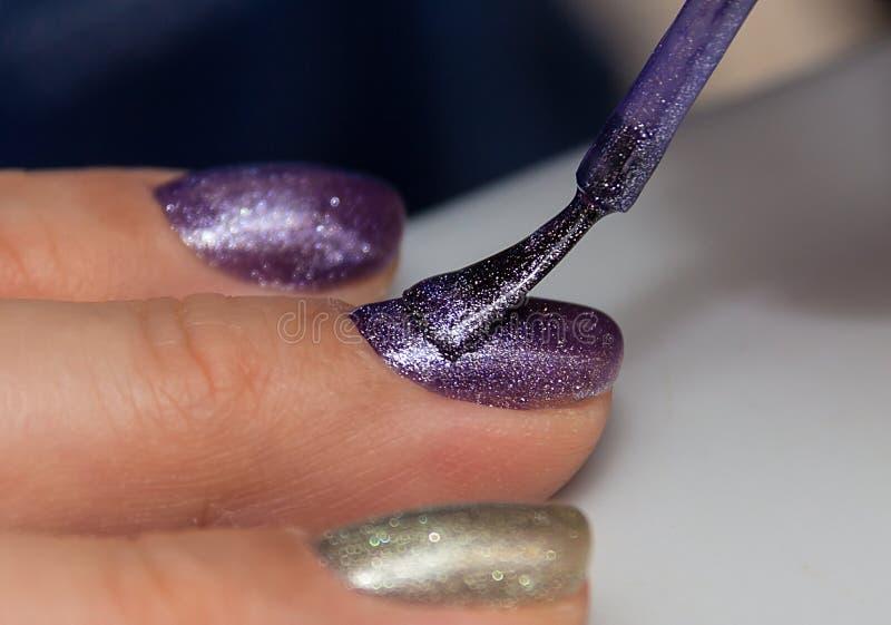 Applicazione dello smalto del gel sulle unghie delle dita immagine stock libera da diritti