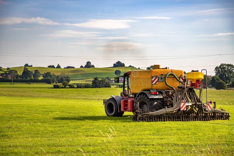 Applicazione di concime su terreno coltivabile arabile con il trattore pesante fotografia stock