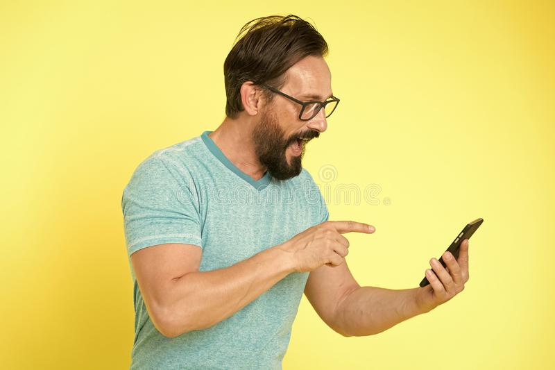Applicazione di download Smartphone allegro di uso dei pantaloni a vita bassa Utente felice dell'uomo dello smartphone Soggiorno  fotografie stock libere da diritti