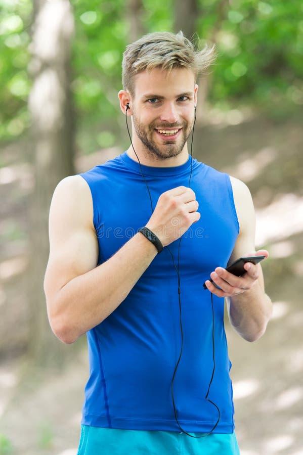 Applicazione di messa a punto Lo sportivo con lo smartphone e l'orologio astuto preparano per il trotto L'addestramento con l'app fotografie stock libere da diritti