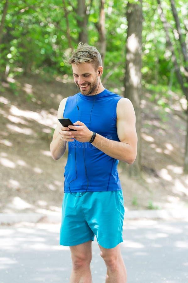 Applicazione di messa a punto Lo sportivo con lo smartphone e l'orologio astuto preparano per il trotto L'addestramento con l'app immagine stock