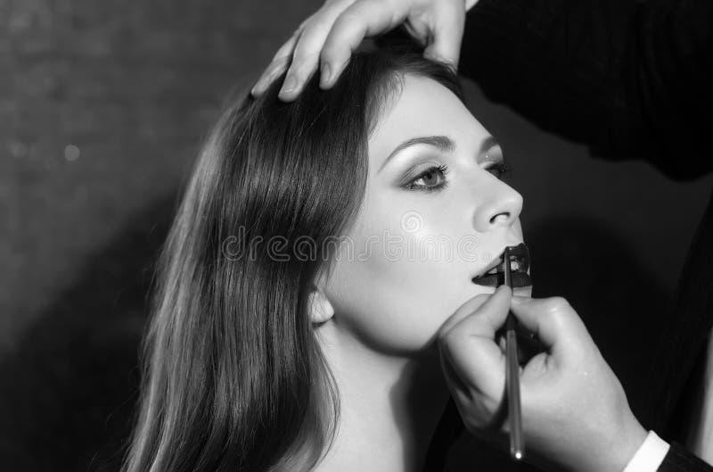 Applicazione di rossetto modello di moda che ottiene le labbra dipinte nel salone di bellezza fotografie stock libere da diritti