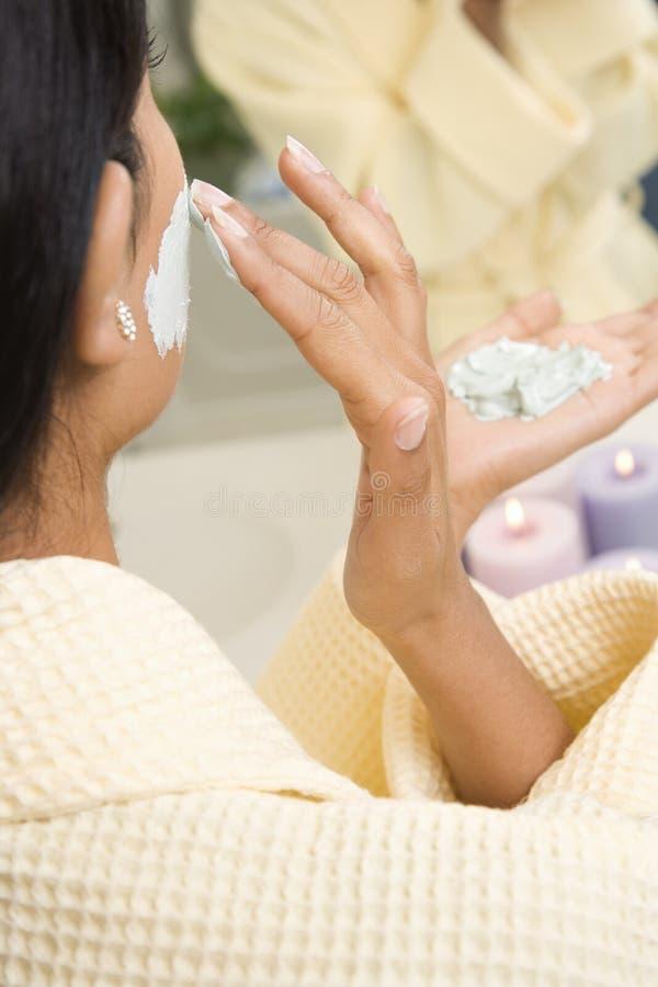 applicera ansiktsbehandling skura kvinnan royaltyfri fotografi