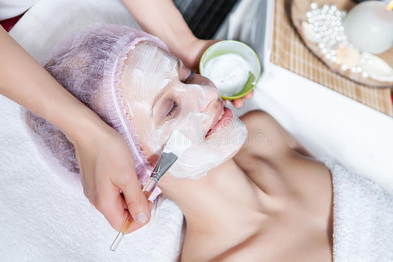 applicera den ansikts- maskeringen för cosmeticianframsida till royaltyfri bild