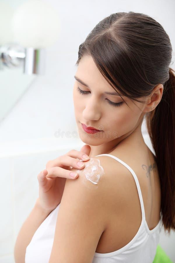 applicera den kräm- skulderkvinnan arkivfoton