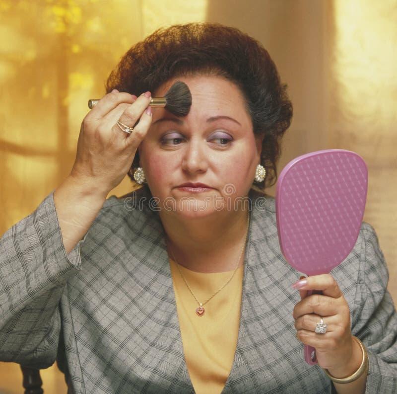 applicera den tunga seende makeupspegelkvinnan arkivfoto