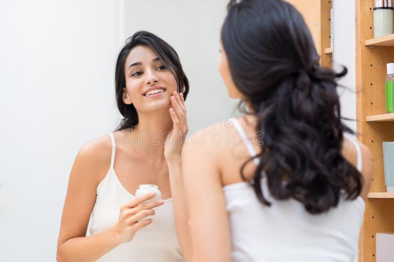 applicera fuktighetsbevarande hudkrämkvinnan royaltyfri foto