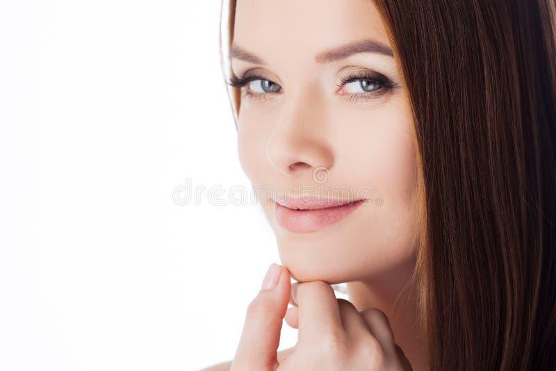 applicera genomskinlig fernissa för omsorgshud Flickan trycker på hennes framsida, närbild Stående av den unga härliga kvinnan royaltyfria bilder
