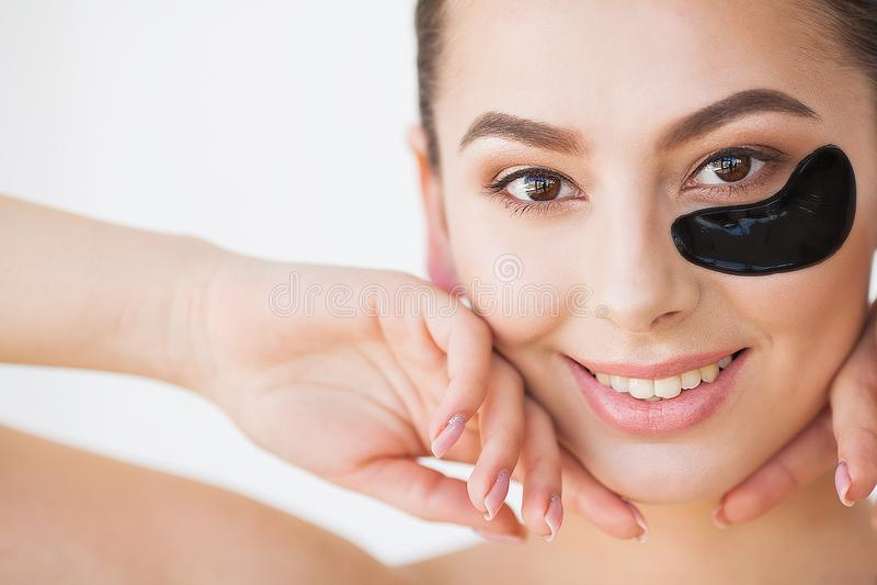 applicera genomskinlig fernissa för omsorgshud Härlig flicka med skönhetsmedelsvartlappar under arkivfoton