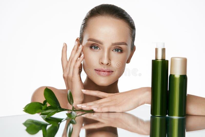applicera genomskinlig fernissa för omsorgshud Härlig kvinna med skönhetframsidan arkivbild