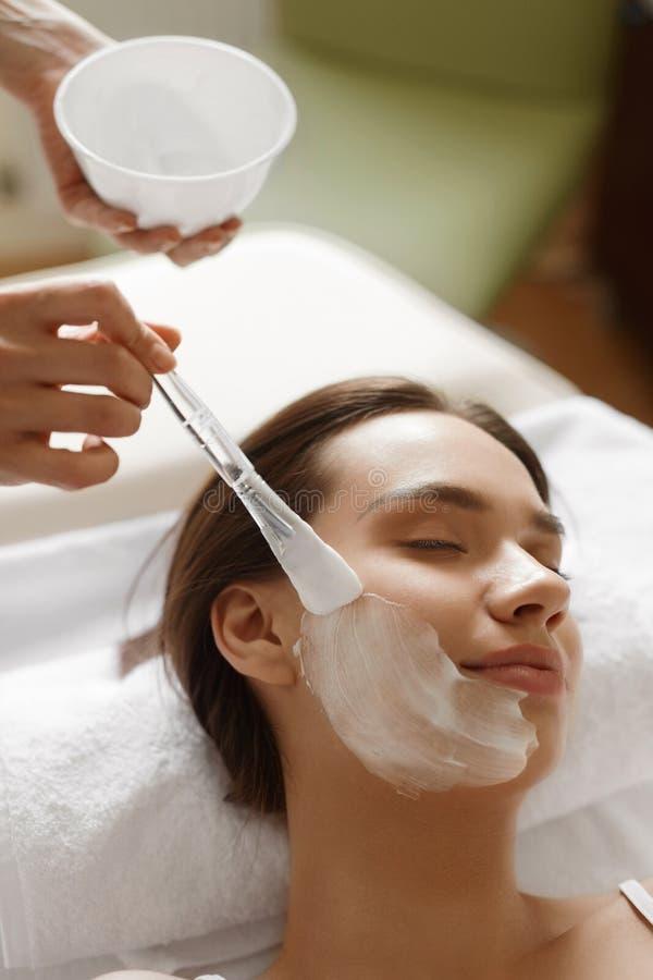 applicera genomskinlig fernissa för omsorgshud Härlig kvinna som får den kosmetiska maskeringen på den Spa salongen arkivbilder