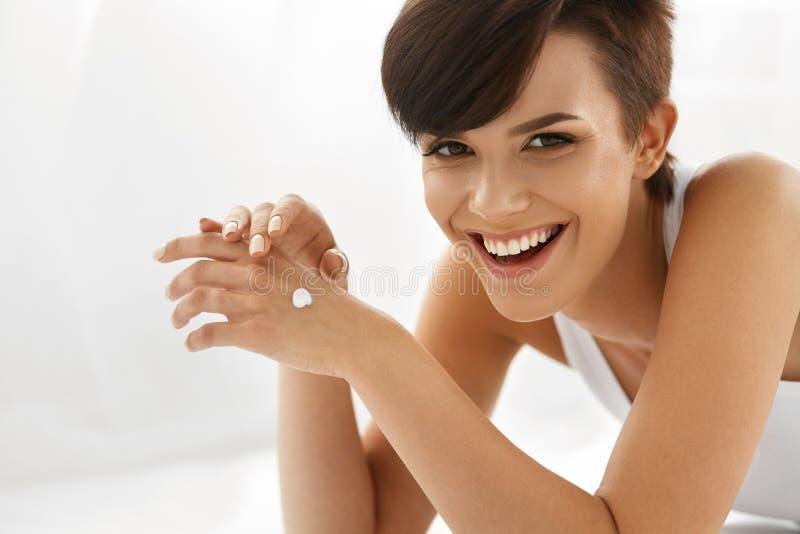 applicera genomskinlig fernissa för omsorgshud Härlig lycklig kvinna med handkräm, lotion förestående royaltyfria foton
