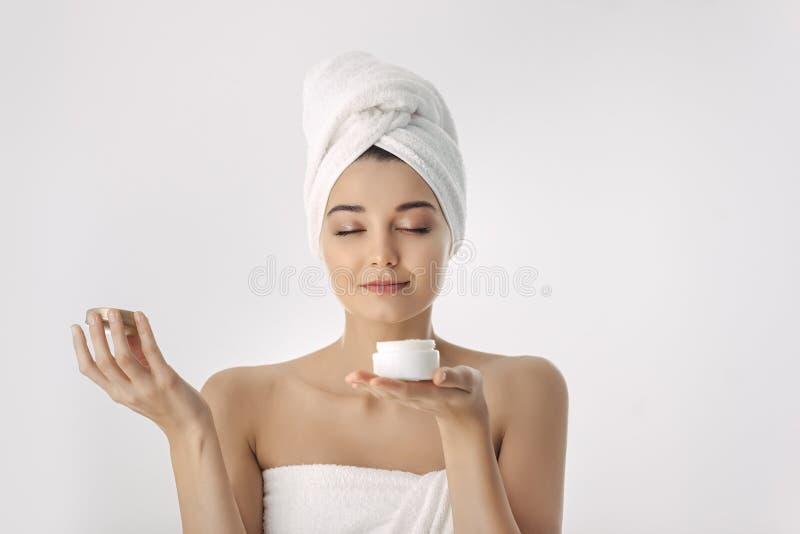 applicera genomskinlig fernissa för omsorgshud Kvinna med naturlig framsidaskönhet som rymmer ansikts- kräm royaltyfria bilder