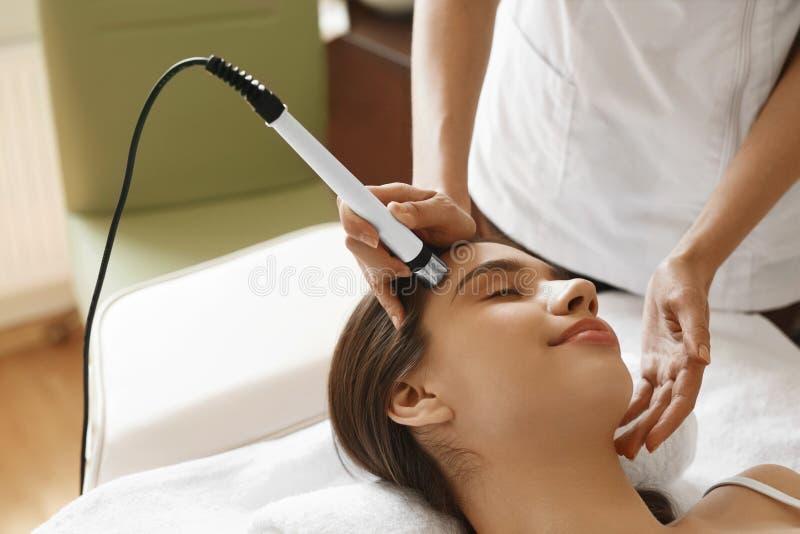 applicera genomskinlig fernissa för omsorgshud Kvinna som får ansikts- syre Jet Peeling Treatment arkivfoto