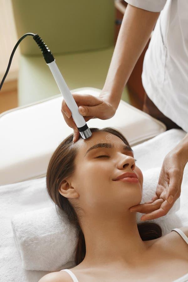 applicera genomskinlig fernissa för omsorgshud Kvinna som får ansikts- syre Jet Peeling Treatment royaltyfri fotografi