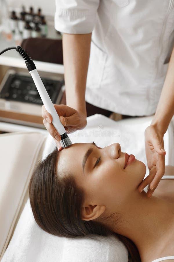 applicera genomskinlig fernissa för omsorgshud Kvinna som får ansikts- syre Jet Peeling Treatment royaltyfri bild
