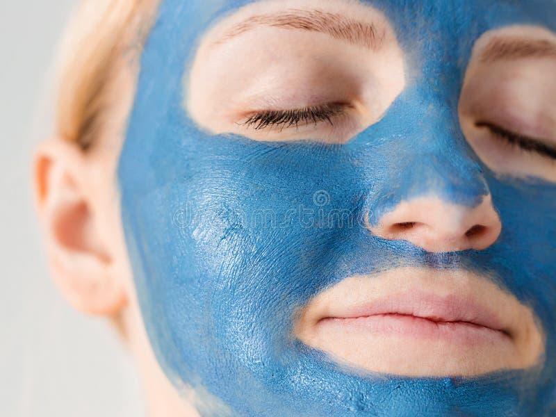 applicera genomskinlig fernissa för omsorgshud Kvinnaframsida med blått slut för leragyttjamaskering upp Flicka som tar omsorg av royaltyfri foto