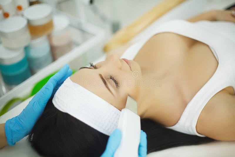 applicera genomskinlig fernissa för omsorgshud Närbild av ansikts- skalning för härlig Cavitation för kvinnahäleriultraljud Ultra arkivfoton