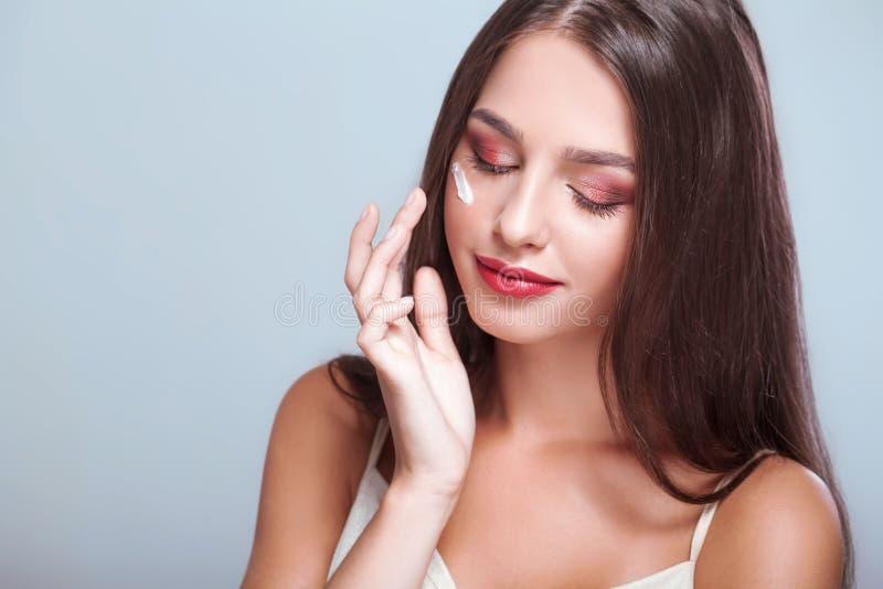 applicera genomskinlig fernissa för omsorgshud Skönhetframsida av kvinnan med skönhetsmedelkräm på framsida _ royaltyfria bilder