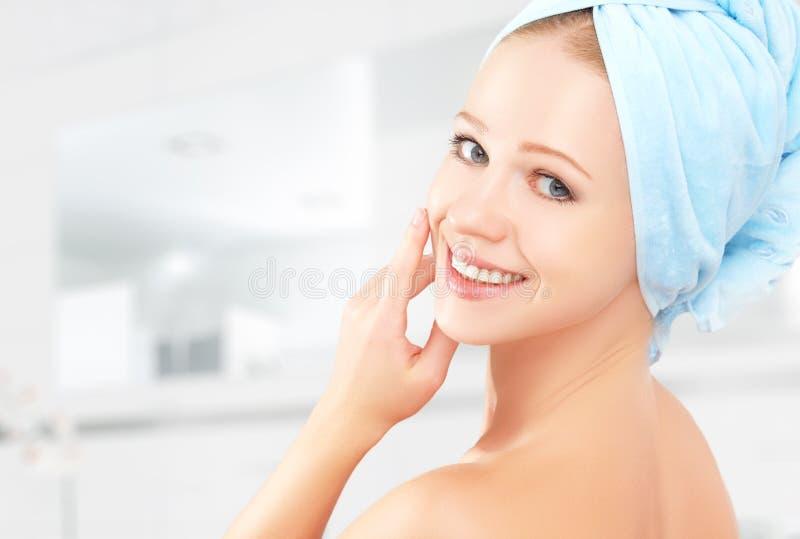 applicera genomskinlig fernissa för omsorgshud ung härlig sund flicka i handduk i badrum royaltyfria foton