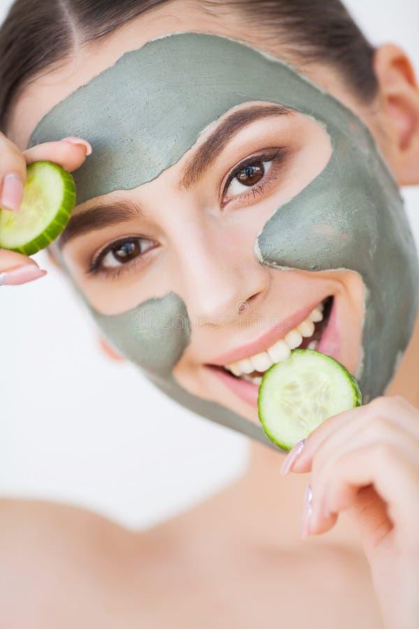 applicera genomskinlig fernissa för omsorgshud Ung kvinna med den hållande gurkan för kosmetisk leramaskering royaltyfri fotografi