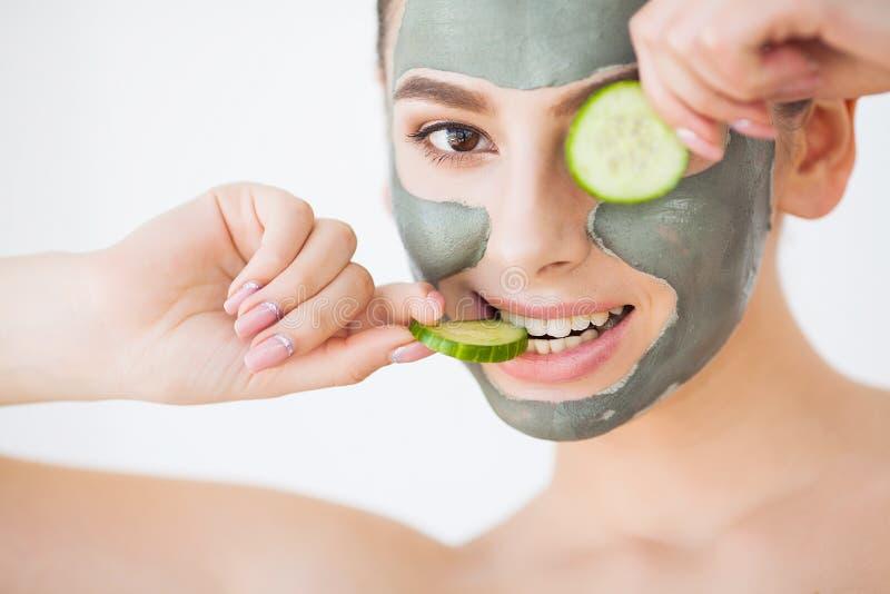 applicera genomskinlig fernissa för omsorgshud Ung kvinna med den hållande gurkan för kosmetisk leramaskering arkivfoton