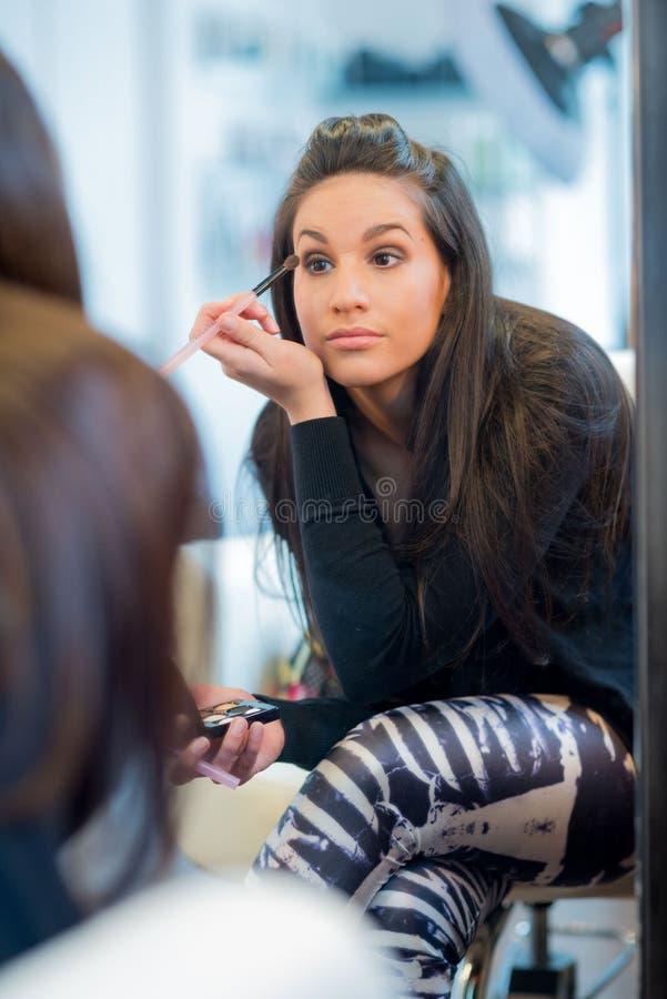 applicera makeupkvinnan arkivbild