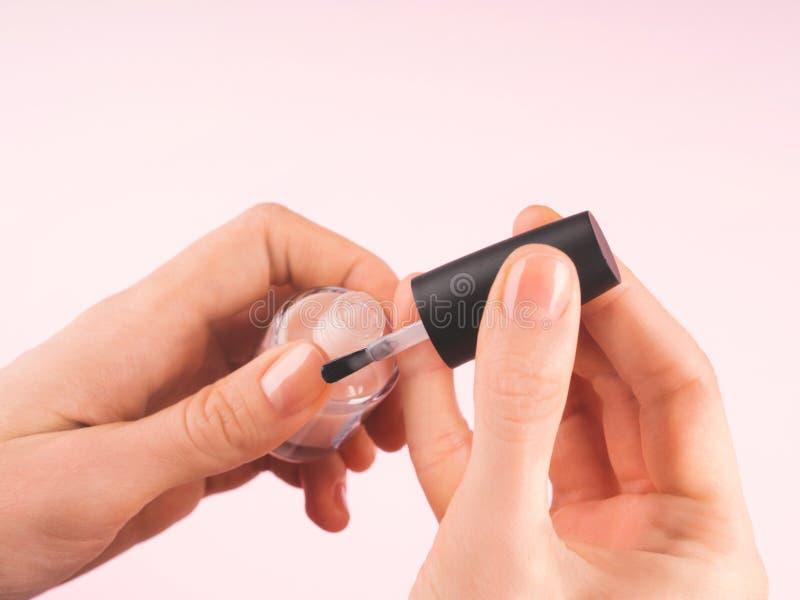 Applicera nakenstudie spika polermedel till kvinnans hand royaltyfria foton