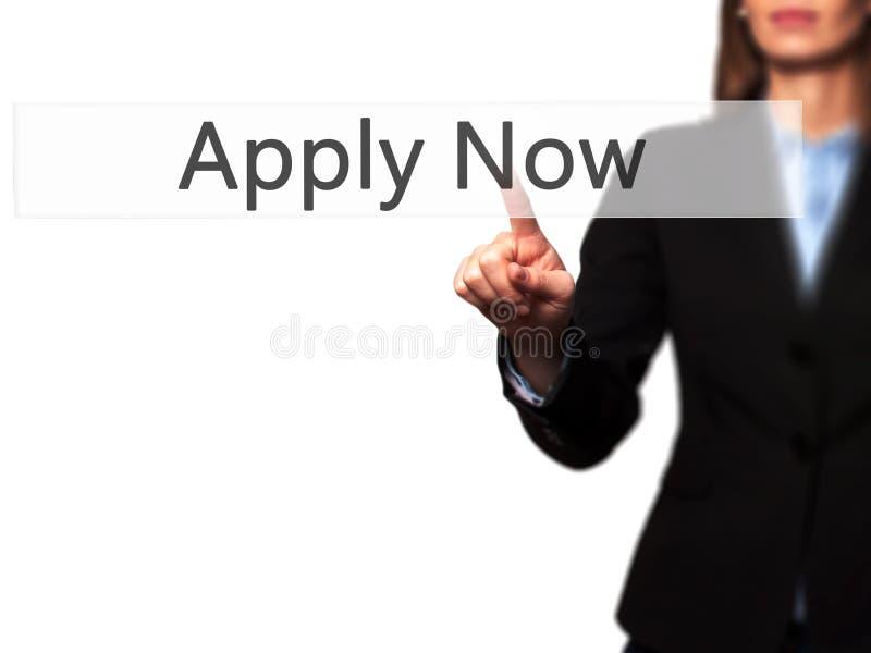 Applicera nu - den isolerade kvinnliga handen som trycker på eller pekar till knappen arkivfoton