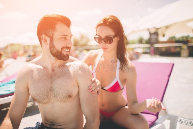 applicera parsuncream Lycklig ung kvinna som applicerar kräm på baksida för pojkvän` s arkivfoto