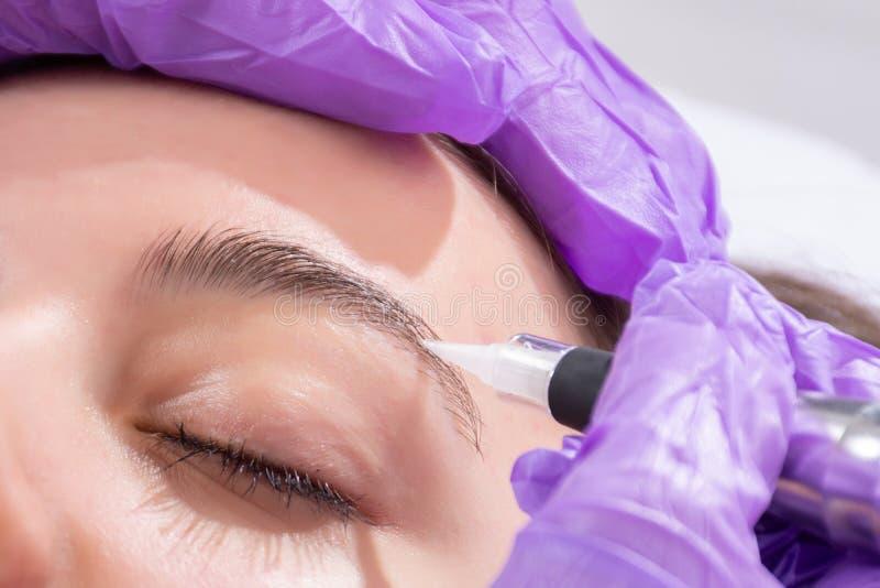 Applicera permanent utgör på ögonbryn i skönhetstudio på härlig flicka arkivbild