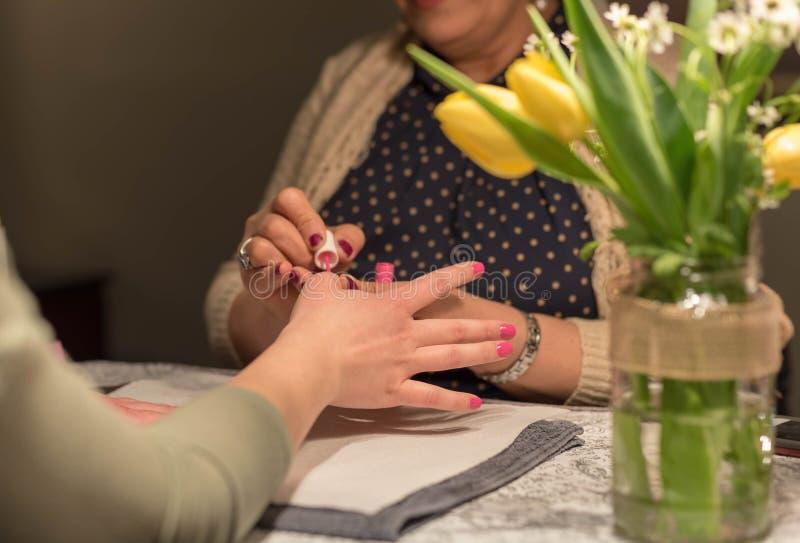Applicera rosa färger spika polermedel på spikasalongen fotografering för bildbyråer