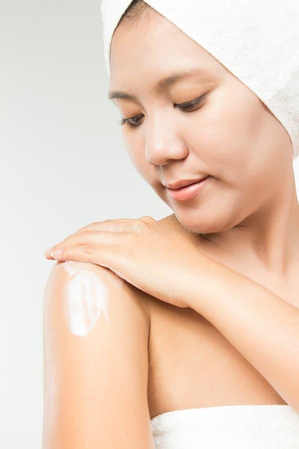 applicera tät bildfuktighetsbevarande hudkräm upp kvinnabarn royaltyfri foto