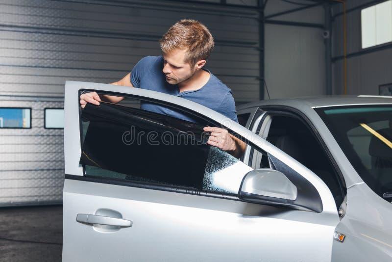 Applicera tona folie på ett bilfönster royaltyfri fotografi