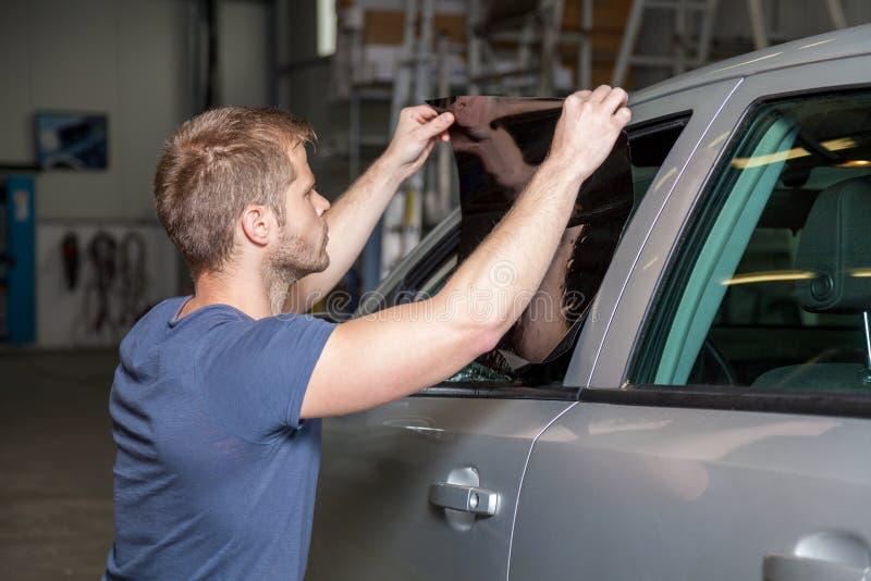 Applicera tona folie på ett bilfönster royaltyfria foton