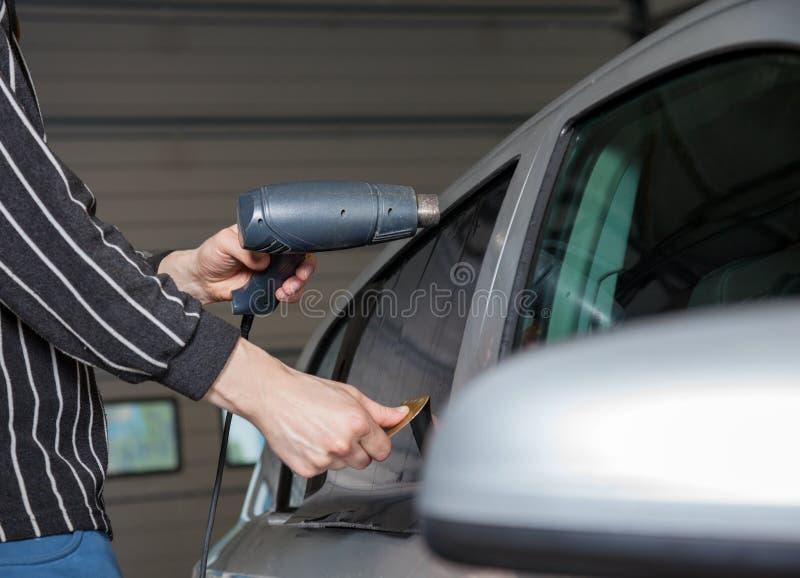 Applicera tona folie på ett bilfönster fotografering för bildbyråer
