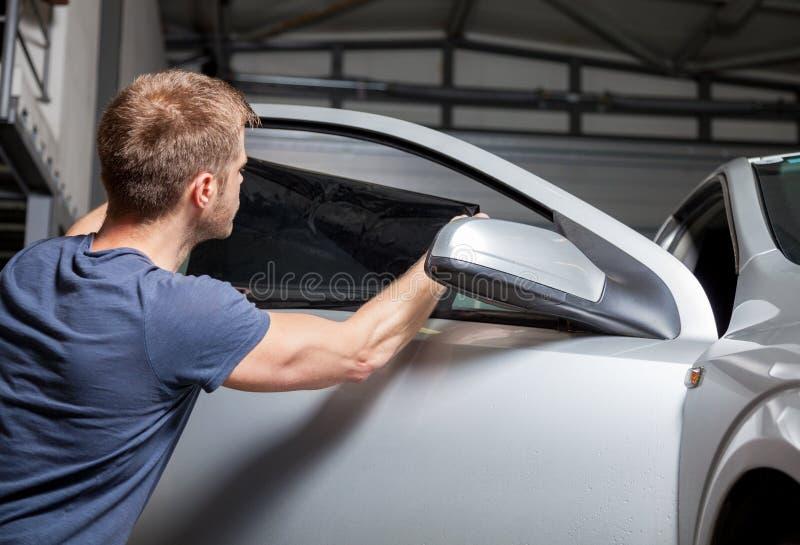 Applicera tona folie på ett bilfönster arkivbilder