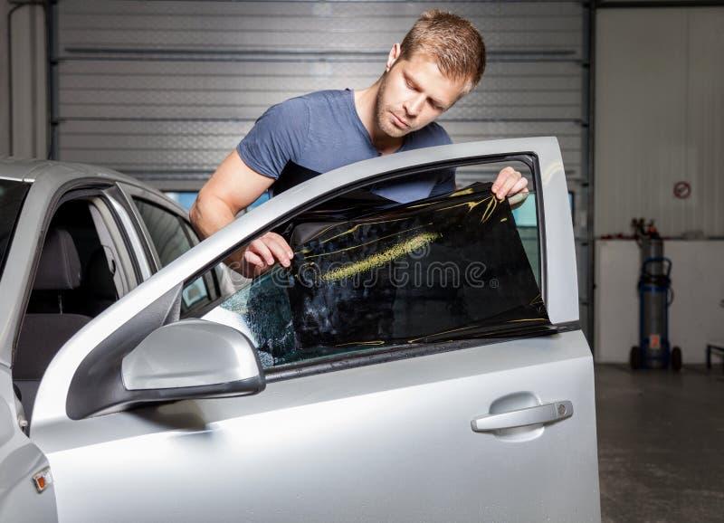 Applicera tona folie på ett bilfönster royaltyfri foto