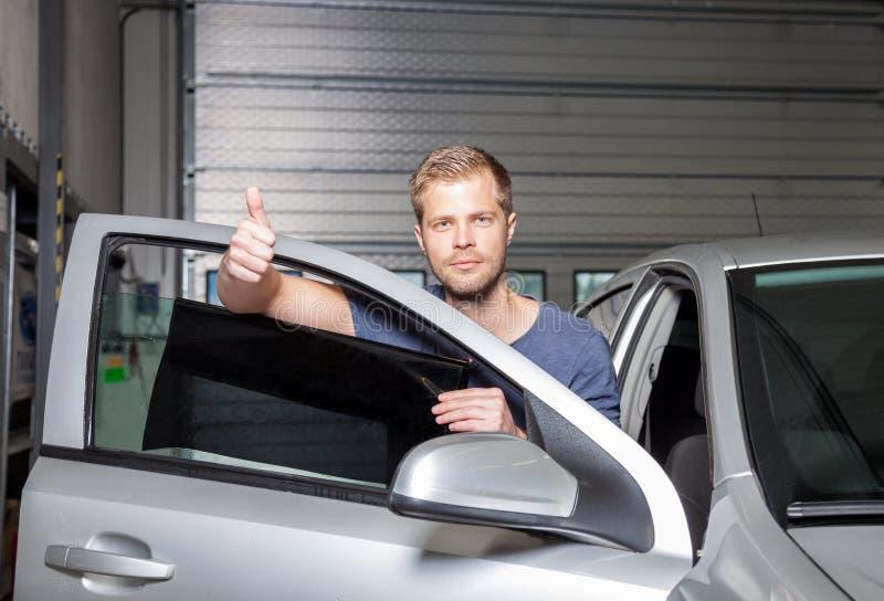 Applicera tona folie på ett bilfönster royaltyfria bilder