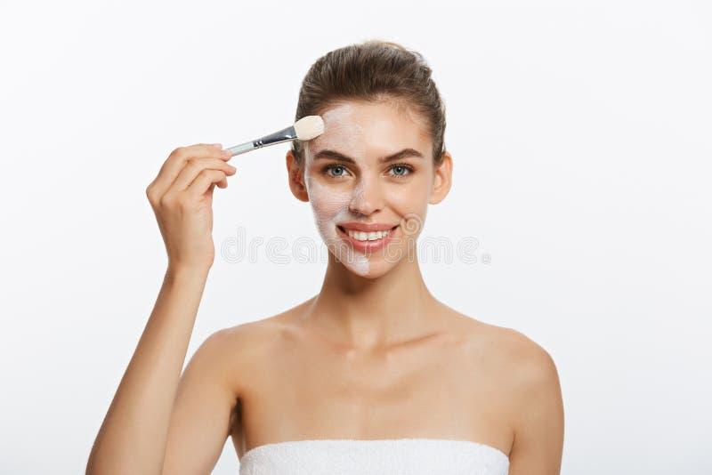 Applicerar den härliga nakna kvinnan för ståenden på den kosmetiska vita leramaskeringen med borsten bakgrund isolerad white Begr royaltyfria bilder