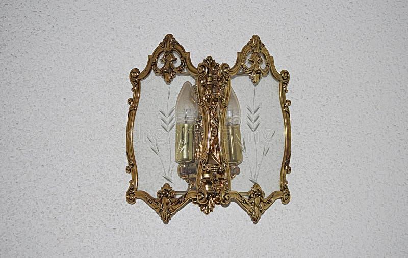 Applichi dorato sulla parete di due lampadine immagine stock