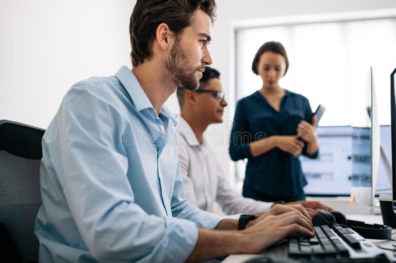 Applikationbärare som i regeringsställning arbetar på datorer arkivbilder