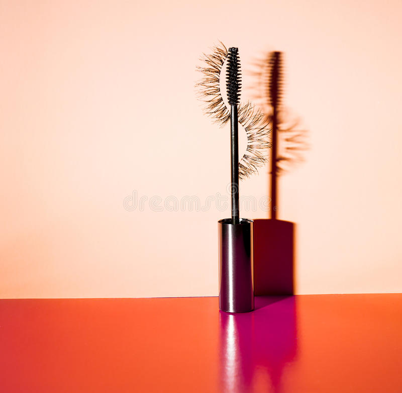 Applikatornwimperntusche und falsche Wimpern mit Schlagschatten auf orange Hintergrund lizenzfreie stockfotografie