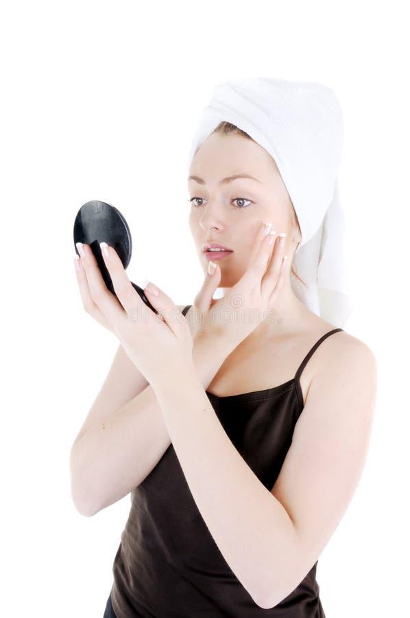 Appling crème sur la peau de visage photographie stock