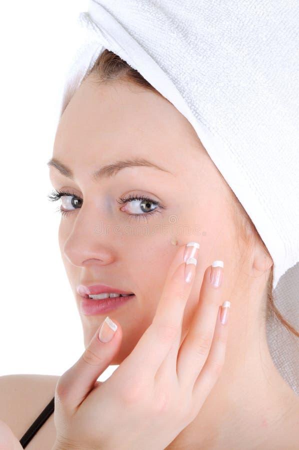 Appling crème sur la peau de visage image stock